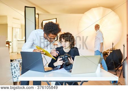 Photo assistant with checklist and photographer on laptop plan photoshoot