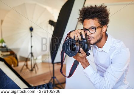 Creative young photographer with reflex camera at the photo shoot