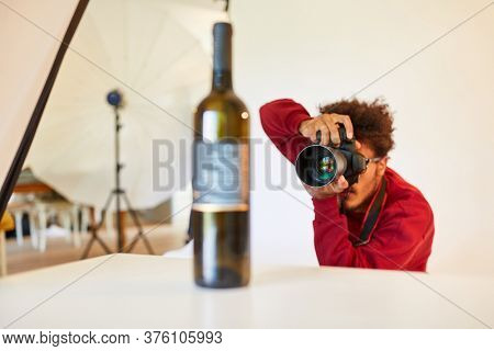 Photographer with SLR camera photographs a bottle as a product