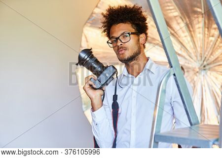 Cool and creative photographer with SLR camera in the photo studio