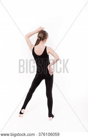Girl Gymnast In A Black Gymnastic Leotard On A White Background Isolated. Young Girl Doing Gymnastic