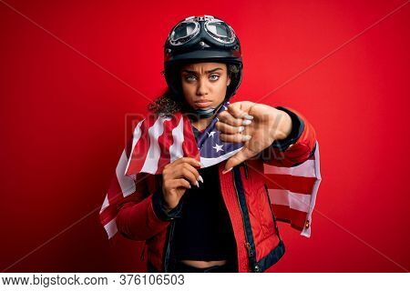African american patriotic motorcyclist girl wearing moto helmet wearing united states flag with angry face, negative sign showing dislike with thumbs down, rejection concept