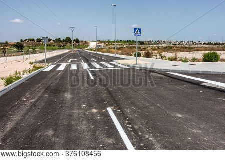 New Road Markings And Road Signs On Freshly Tarmacked Roads On Spanish Urbanisation