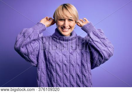 Young blonde woman with short hair wearing winter turtleneck sweater over purple background Smiling pulling ears with fingers, funny gesture. Audition problem