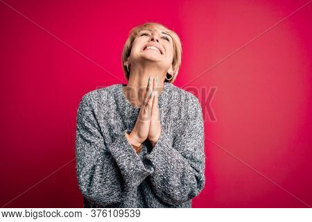 Young blonde woman with modern short hair wearing casual sweater over pink background begging and praying with hands together with hope expression on face very emotional and worried. Begging.