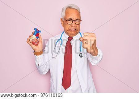 Middle age senior grey-haired cardiologist doctor man holding professional medicine heart annoyed and frustrated shouting with anger, crazy and yelling with raised hand, anger concept
