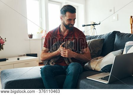 Handsome Young Man In Casual Clothing Bonding With Domestic Cat And Smiling While Spending Time Indo