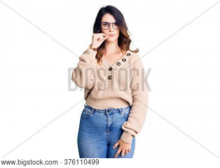 Beautiful young brunette woman wearing casual clothes and glasses mouth and lips shut as zip with fingers. secret and silent, taboo talking