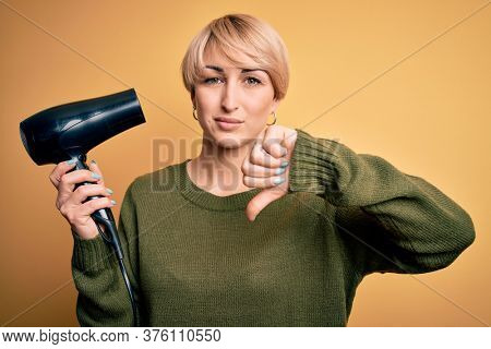 Young blonde woman with short hair drying her hair using hairdryer over yellow background with angry face, negative sign showing dislike with thumbs down, rejection concept