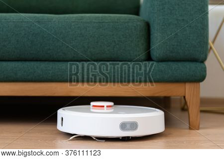 Robotic Vacuum Cleaner Cleaning The Living Room Under The Sofa. Housekeeping Help, New Technology, S