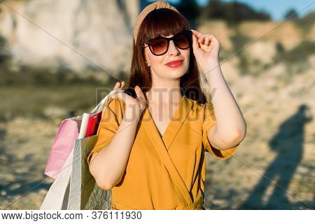 Close Up Portrait Of Elegant Glamour Young Woman In Sunglasses And Yellow Clothes, Smiling With Shop