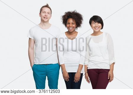 Portrait of young multi-ethnic friends in casuals standing side by side over white background