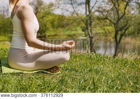 Close-up Of A Girl Meditating In The Lotus Position In The Fresh Air In The Park. The Girl Relaxes A