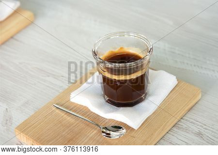 Black Coffee In A Glass Cup On A Wooden Tray. Morning Americano With Foam On A Wooden Table.