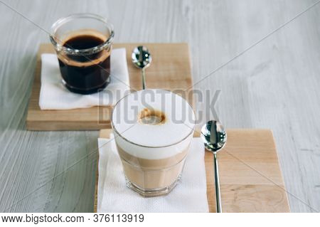 Black Coffee And Cappuccino In A Glass Cup On A Wooden Tray. Morning Americano With Foam On A Wooden