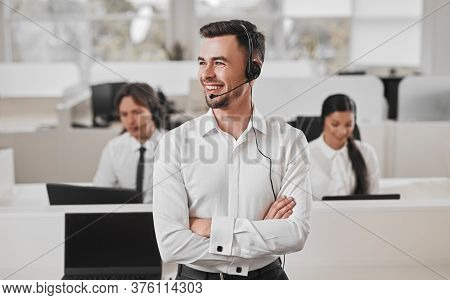 Confident Man With Crossed Arms Smiling And Looking Away While Answering Client Call During Work In