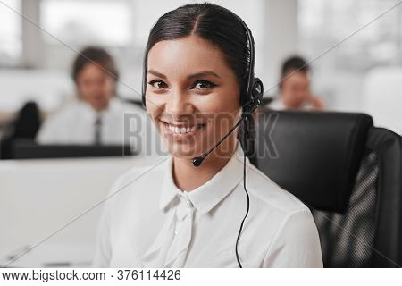 Cheerful Ethnic Woman With Headset Smiling And Looking At Camera While Speaking With Customer During