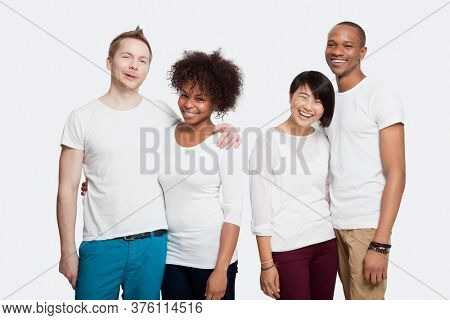 Portrait of two cheerful young couples in casuals standing together over white background