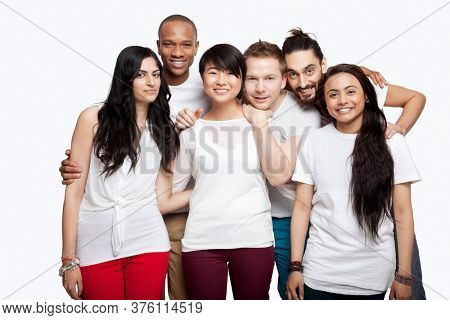 Portrait of young multi-ethnic friends in casuals smiling over white background
