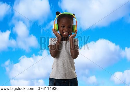 Music, Childhood And Technology Concept.lovely Happy Little African Girl With Headphones Over Blue S