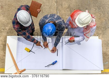 Top View Of Engineering Team In Site Manager Field Engineer And Foreman Looking At Construction Pape