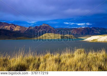 Huge lake with azure water, arid steppe of Patagonia and the steep slopes of cold mountains. Los Glaciares Park in Argentina. The concept of active, extreme and photo tourism