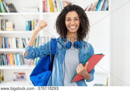 Cheering Latin Female Student With Curly Hair And Paperwork At Classroom Of University