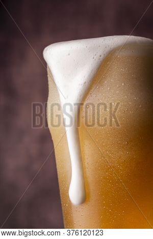 Detail Of Pint Of Ice Cold Pale Beer With Froth Leaking Over The Glass