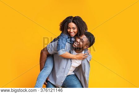 Cheerful African Couple Having Fun Together, Guy Piggybacking His Girlfriend Over Yellow Background,