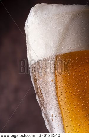 Pint Of Ice Cold Light Beer With Froth Leaking Over The Glass