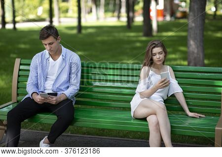 Gadget Addiction And Relationship Problems. Millennial Couple With Smartphones Sitting On Bench At P