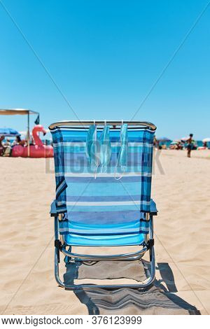 some surgical masks hanging on a blue deck chair on the beach, with the sea in the background