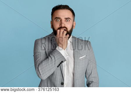 Stress Management Concept. Scared Businessman Biting Fingernails In Panic On Blue Background