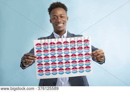 Happy Smiling African Voter Holding Stickers With I Voted Today Text Over Blue Background