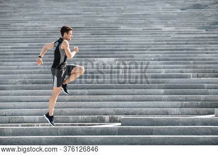 Athlete Runs And Jumps In Morning. Young Man In Sportswear Jogging On Stairs In Summer, Free Space,