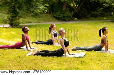 Group Of Diverse Girls Doing Cobra Yoga Pose On Their Morning Practice At Green Park, Panorama