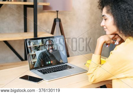 Side View Of Biracial Girl Talks Via Video Call With An African-american Male Colleague Or Friend On