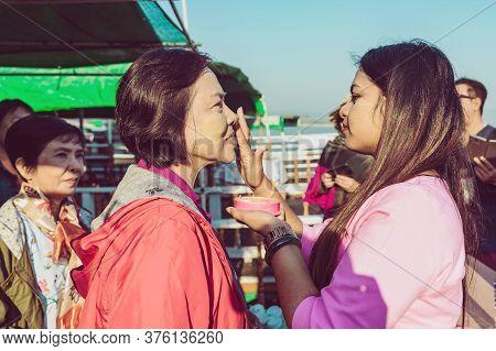 Mandalay-myanmar, January 20, 2019 : Female Tourist Guide Paints Tanaka Powder On Female Tourist Fac