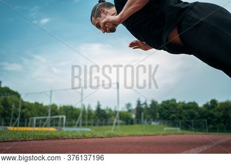Young Athlete Push Up And Jump At Stadium Outdoor