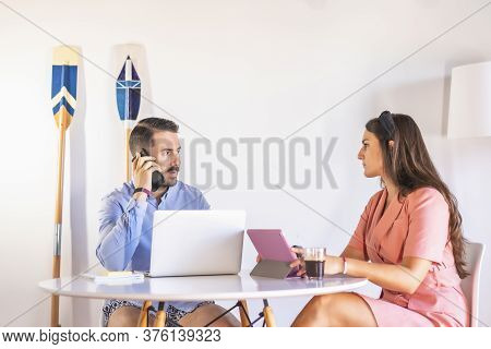 A Young Couple Are Teleworking At Home, A Boy In A Blue Shirt And A Girl In A Pink Suit. With A Lapt