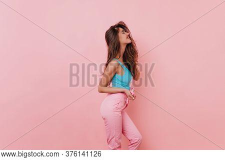 Slim Lovable Girl With Long Hair Posing In Studio. Portrait Of Winsome Female Model In Blue Tank-top
