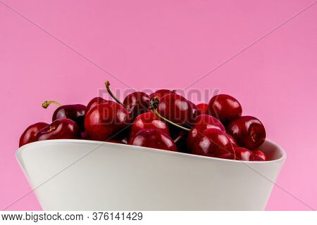 Collection Of Many Cherries In White Ceramic Bowls On Pink Background Isolated