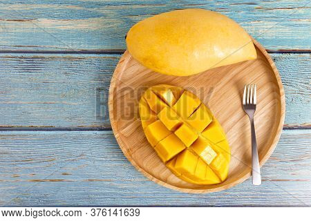 Yellow Half  Mango With Small Fork. Mango Fruit Cubes On The Wooden Table. Tropical Fruit Asia. Fres