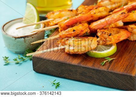 Grilled Shrimp Skewers Or Langoustines Served With Lime, Garlic And Sauce On A Light Blue Concrete B