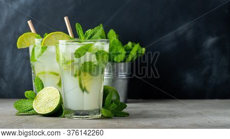 Two Homemade Lemonade Or Mojito Cocktail With Lime, Mint And Ice Cubes In A Glass On A Dark Stone Ta