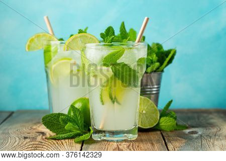 Two Homemade Lemonade Or Mojito Cocktail With Lime, Mint And Ice Cubes In A Glass On A Light Stone T