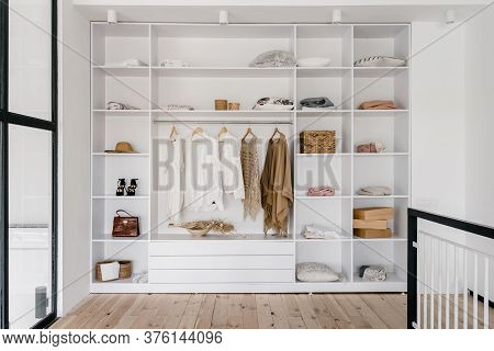 Modern And Large Wardrobe In Dressing Room With Fashionable Woman Clothes