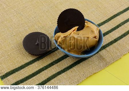Two Dark Chocolate Peanut Butter Cups And Peanut Butter In Blue Dipping Bowl On Brown Woven Place Ma