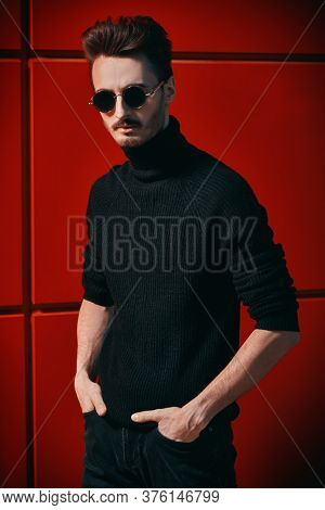 Urban style. Portrait of a stylish young man in black pullover and round mirror sunglasses posing on a street by the yellow industrial wall. Male fashion. Copy space.