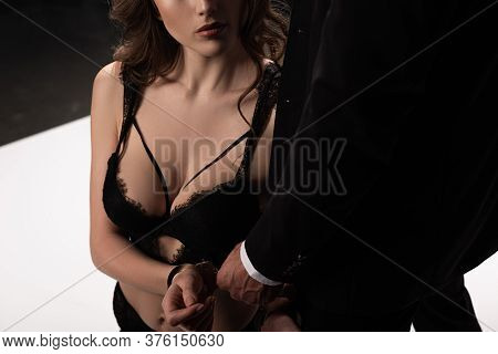 Cropped View Of Dominant Man Touching Handcuffs On Submissive Woman In Bra